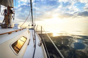 White,Yacht,Sailing,In,A,Still,Water,At,Sunset.,A